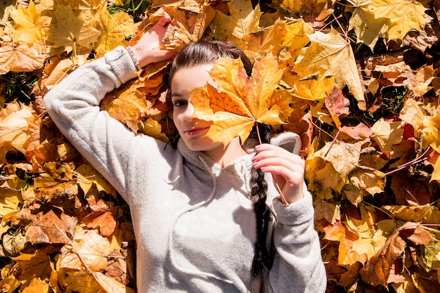 The girl lies on the autumn leaves