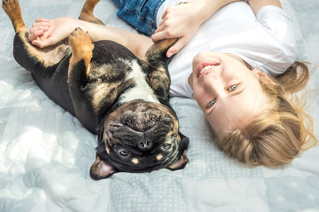Girl lies on the bed in an embrace with her dog of the french bulldog breed