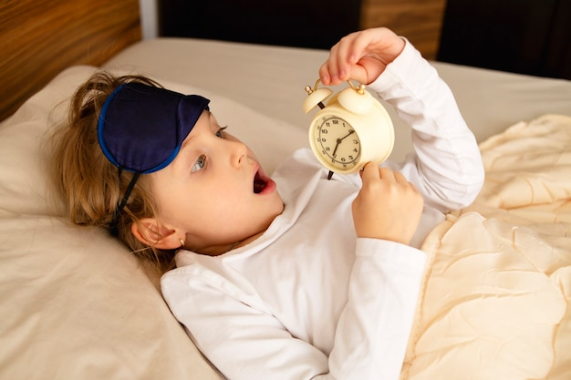 The girl lies in bed surprised and shocked, scared, is late, the alarm clock is in her hands.