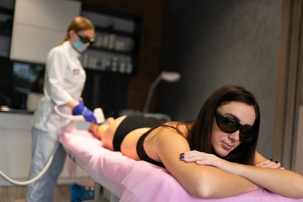 Girl lies on the couch when she is undergoing laser hair removal