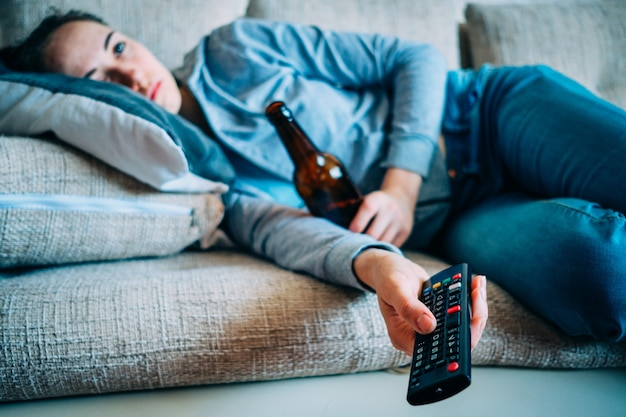 The girl lies on the couch with a bottle of alcohol and a remote control from the tv.