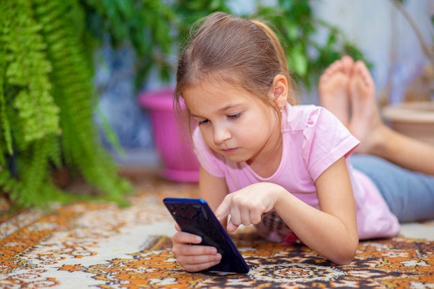 A girl lies on the floor and plays on a smartphone. child and technology. stay home.