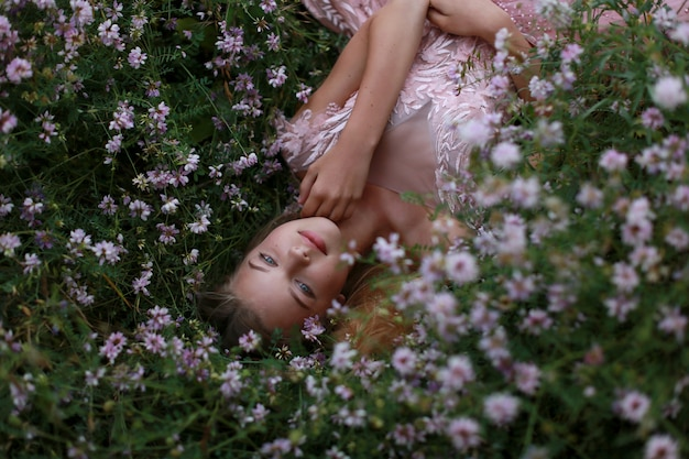 Girl lies in flowering grass