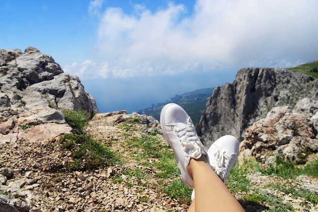 The girl lies on the grass in sneakers shoes with views of the mountains