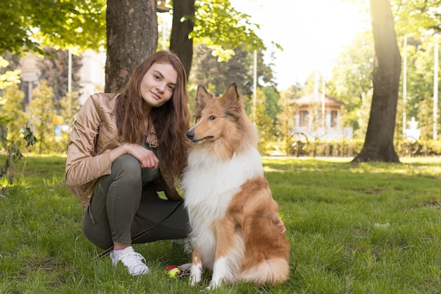 Girl lies on the grass with her dog