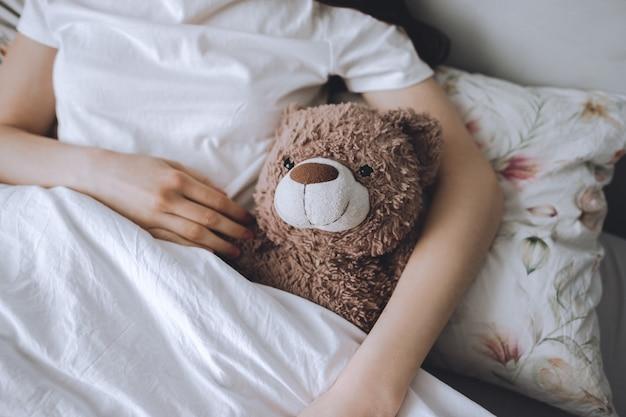 Девушка лежит в постели под одеялом с плюшевым мишкой