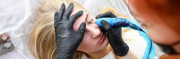 Девушка лежит в салоне на процедуру перманентной брови. эффект после аппаратной татуировки. боль и отек иногда возможны. женщина с помощью машины создает линию с десятками микро-проколов
