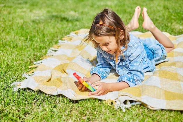 女の子は屋外の芝生の毛布の上に横たわって、それをポップで遊んだり、子供の手はカラフルなポップで遊んだり、晴れた夏の日、夏の休暇に家の裏庭でおもちゃをいじったりします。