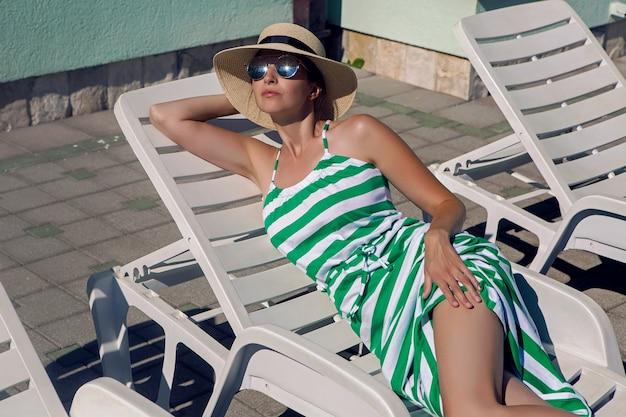 女の子はプールのそばの緑の縞模様のドレスと帽子の寝椅子に横たわっています