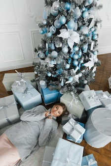 Девушка лежит на полу, в окружении подарков, возле новогодней елки, вид сверху, новогодняя концепция