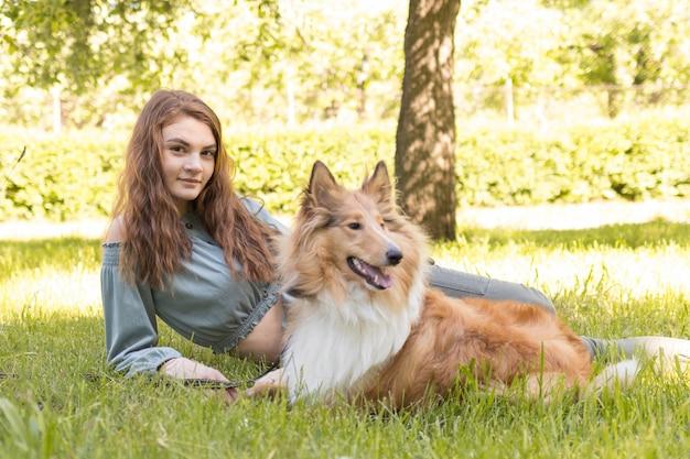 Девушка лежит на траве со своей собакой
