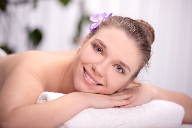 The girl lies in the spa salon and smiling.