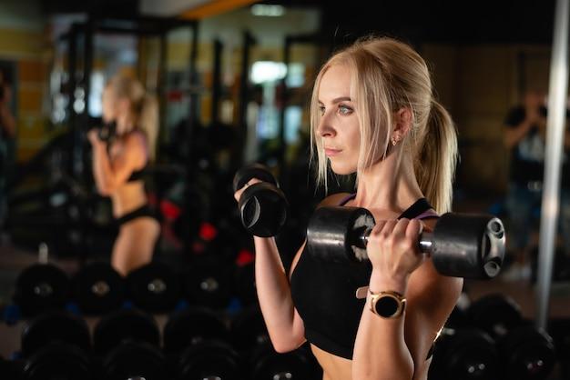 소녀는 두 개의 덤벨을 들어 올리고 손 근육 운동, 아름다운 섹시하고 운동 선수