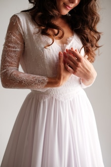A girl in a light dress folded her arms across her chest. hands of the bride gently pink dress