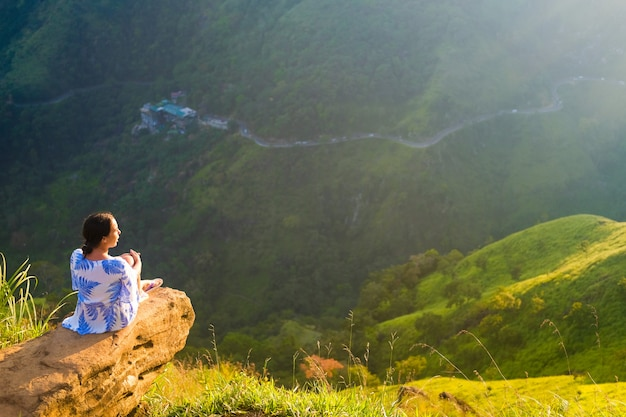 A girl in a light dress sitting on a stone on the edge of a cliff. mountain view from a height.