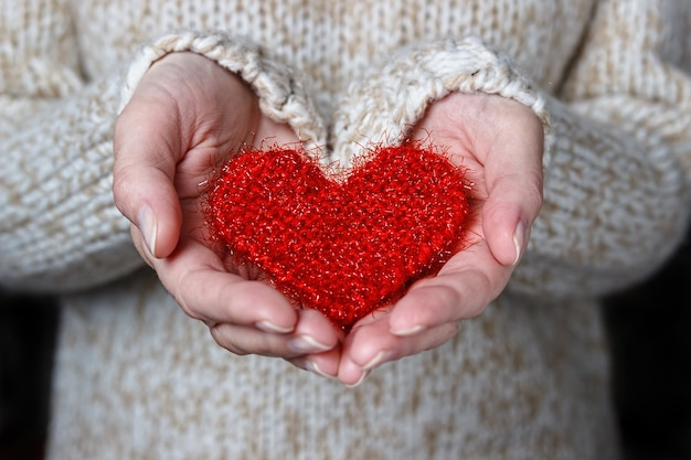 Girl in a light sweater gives a knitted heart.