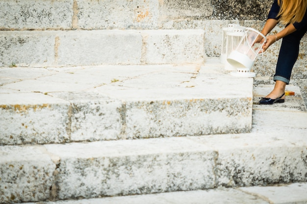 A girl lighting candles on granite stairs