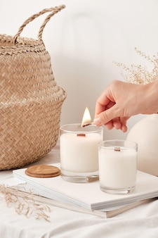 Girl lights soy wax candles with a wooden wick handmade candles