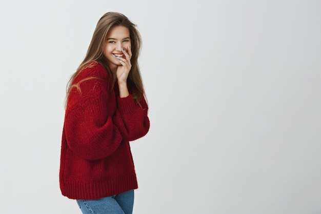 Girl likes to get attention. portrait of emotive good-looking female in loose red sweater, laughing or chuckling while covering mouth with hands and standing in profile