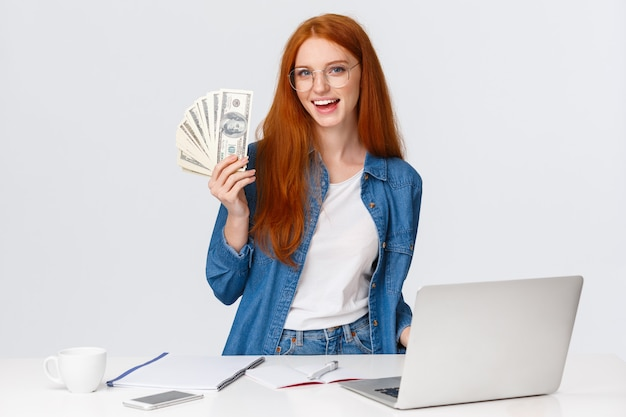 Girl likes her new work, got promoted and receive first paycheck. attractive sassy redhead woman in glasses, standing near working table, laptop, holding money, big cash