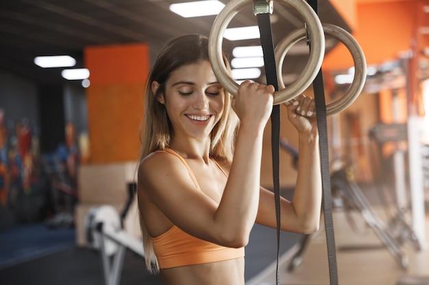 女の子は喜んで笑顔で、クロスフィット体操リングを保持するのが好きです。