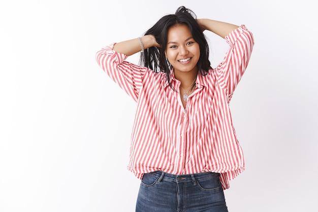 Alla ragazza piacciono i fine settimana pigri. ritratto di giovane donna asiatica spensierata rilassata e gioiosa che gioca con i capelli tenendosi per mano sulla testa e sorridendo gioiosamente sentendosi bene ed energizzata sul muro bianco