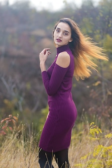 Girl in lilac dress on nature in autumn, portrait of a beautiful girl in the autumn in the forest