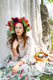 Girl in a linen dress. with a wreath of flowers on her head.