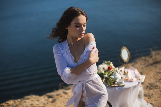 Girl in lingerie on top of a mountain overlooking the ocean. charges of the bride, bride's morning.
