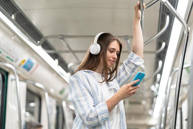 소녀는 무선 인터넷 연결을 통해 지하철에서 음악을 듣고 스마트폰을 사용합니다.
