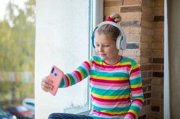 소녀는 이어폰으로 음악을 듣고 셀카를 찍습니다.