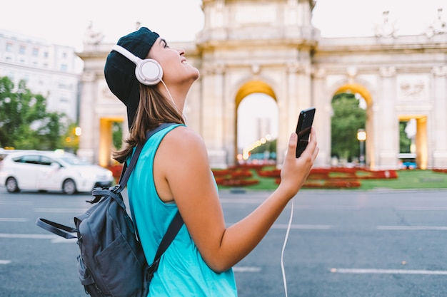 Girl listening to music in front of the puerta de alcala in madrid