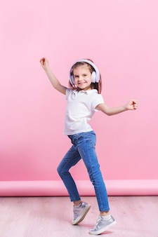 Girl listening to music in headphones an dance on pink . cute child enjoying happy dance music, close eye's and smile posing