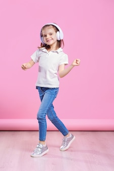 Girl listening to music in headphones an dance on pink wall.