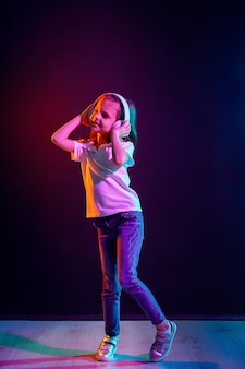 Girl listening to music in headphones on dark colorful . neon light. dancing girl. happy small girl dancing to music. cute child enjoying happy dance music.