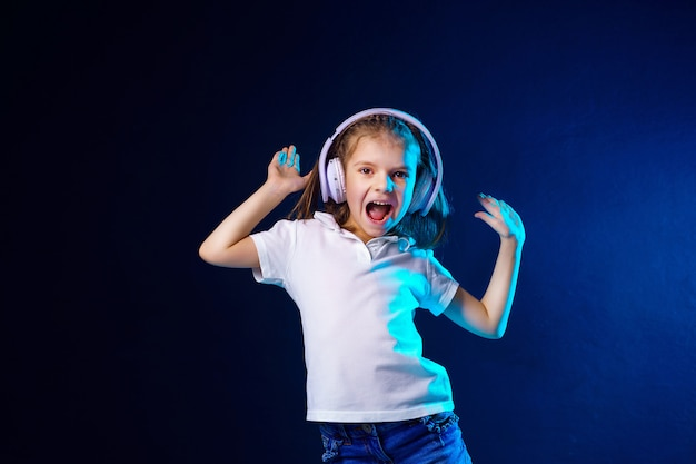 Girl listening to music in headphones on dark colorful wall. cute child enjoying dance music,