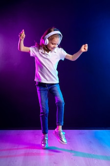 Girl listening to music in headphones on dark colorful wall . dancing girl. happy small girl dancing to music. cute child enjoying happy dance music.