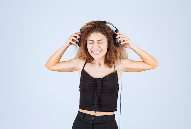 Girl listening to the music on headphones and dislike it.