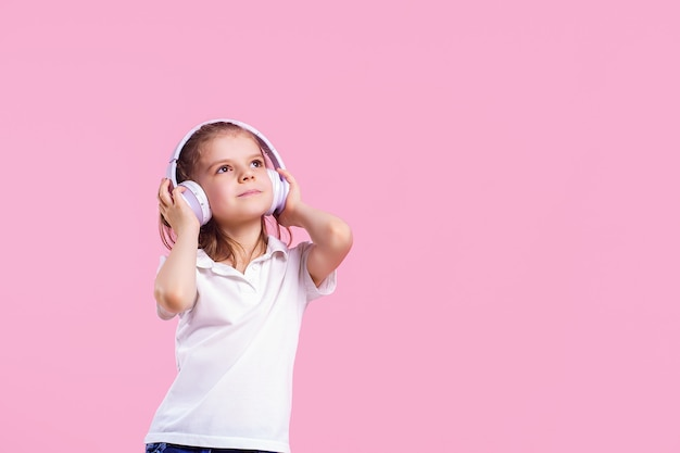 Girl listening to music in headphones on pink wall.