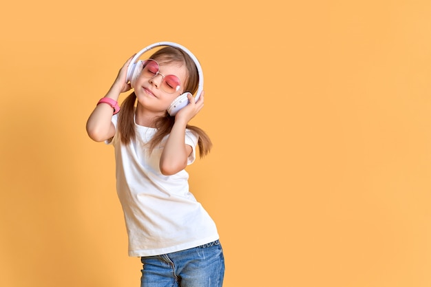Girl listening to music in headphones on yellow . cute child enjoying happy dance music, close eye's and smile posing