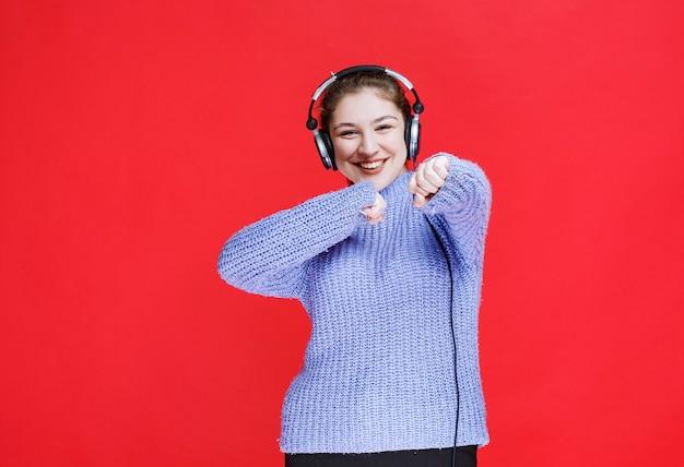 Ragazza che ascolta la musica alle sue cuffie e si diverte.
