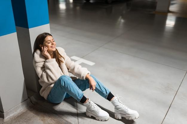 地下駐車場で音楽を聴いている女の子