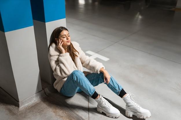 ワイヤレスヘッドフォンで音楽を聴いている女の子
