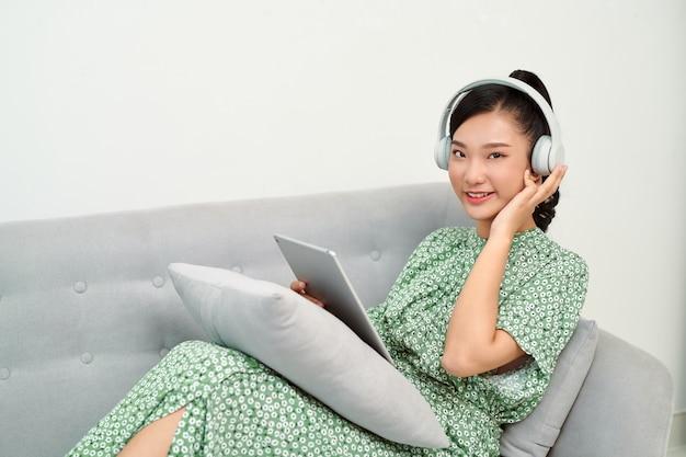 Девушка слушает музыку онлайн с планшетом, сидя на диване в гостиной дома