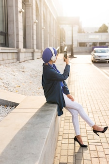 Girl listening to music through headphones outside with copy space