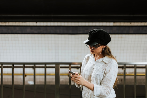 Girl listening to music while waiting for a train