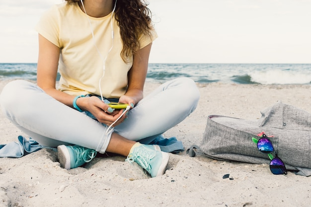 Girl listening to music with headphones on the beach