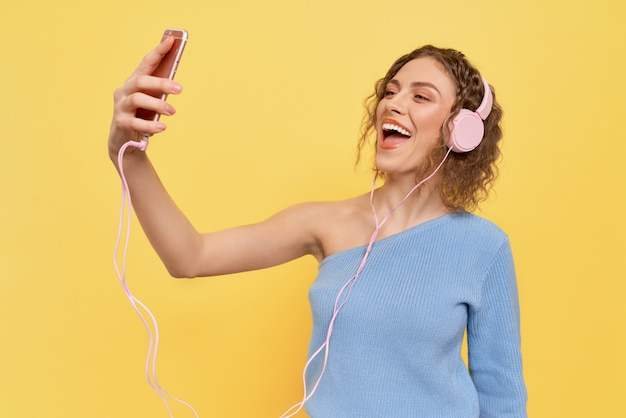 Girl listening to music with headphones, smiling.