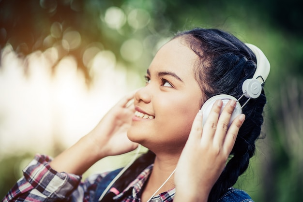 Girl listening music with her headphones in the forest