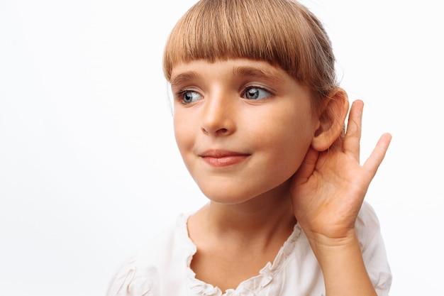 白い壁で聴いている女の子 Premium写真